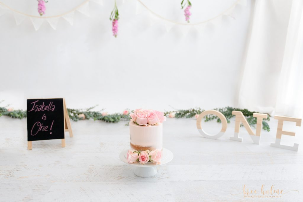 Choosing your cake smash decorations and background colour scheme for your baby girls 1st birthday cake smash portrait session with Bree Hulme PHotography